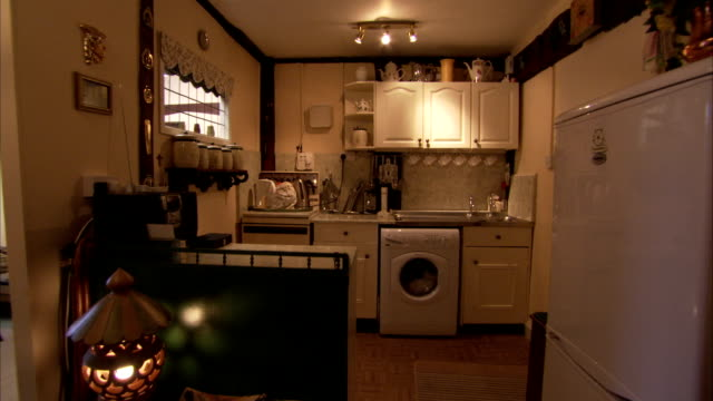 vídeos de stock, filmes e b-roll de a washing machine fits under cabinets in a small kitchen. available in hd. - cabinet