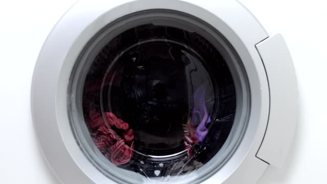 washing machine turning with laundry - laundromat stock videos & royalty-free footage