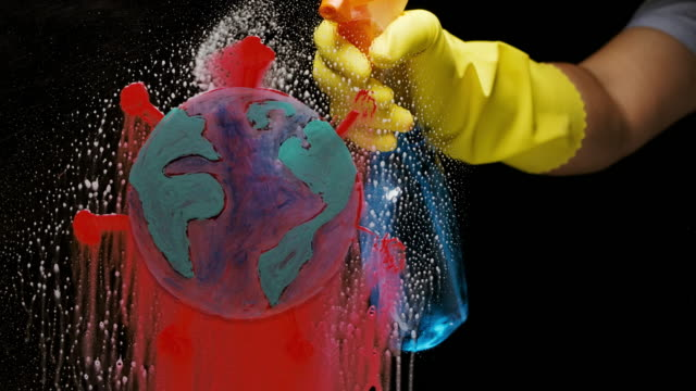 washing out coronavirus from the world, shot of a hand with gloves spraying washing cleaning glass with the icon of red dangerous covid 19 from the world -  covid 19 awareness concept with virus and globe icon. - westernisation stock videos & royalty-free footage