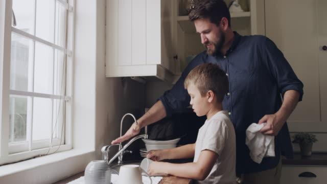 vídeos de stock e filmes b-roll de washing the dishes under the watchful eye of dad - lava loiças
