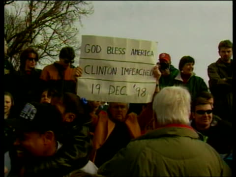 stockvideo's en b-roll-footage met clinton impeachment vote:; b)20.40: bill neely itn usa: washington: ext banner held 'god bless america clinton impeached 19 dec '98' people... - itv evening bulletin