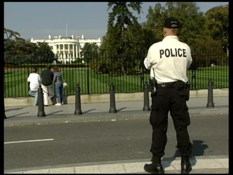 washington dc: police officer standing guard on road next white house lms sniper on roof of white house 'stop' barrier raised into position - sniper stock videos & royalty-free footage