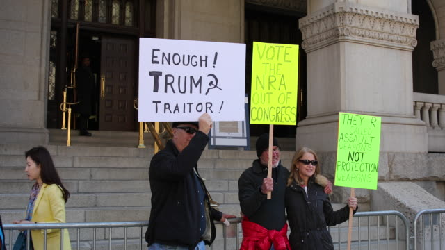 a protester holds a sign outside the trump hotel reading enough trump traitor during the march for our lives rally on march 24 2018 in washington dc... - march for our lives stock videos and b-roll footage