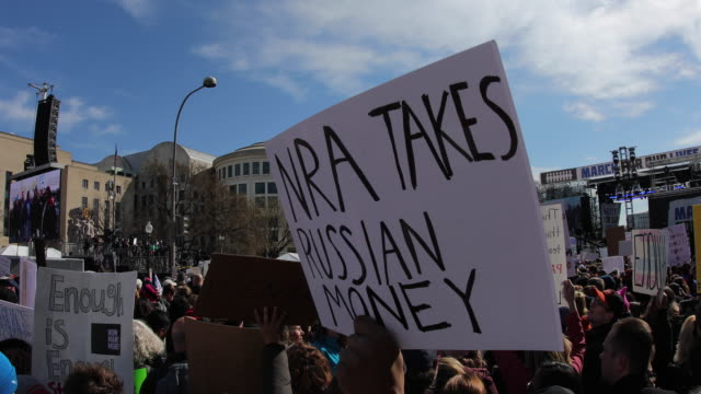 a protester holds a sign reading nra takes russian money protesters participate in the march for our lives rally on march 24 2018 in washington dc... - march for our lives stock videos and b-roll footage