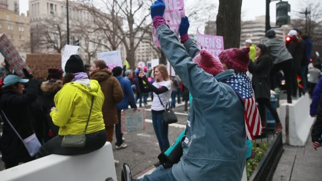 vídeos de stock e filmes b-roll de a woman wearing a pussy hat cheers on fellow marchers while sitting on a concrete barrier during the women's march on washington more than 500000... - chapéu