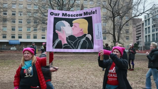 vídeos de stock, filmes e b-roll de two women hold a sign depicting putin and trump kissing with the words our moscow mule more than 500000 women's march participants marched in the... - 2017