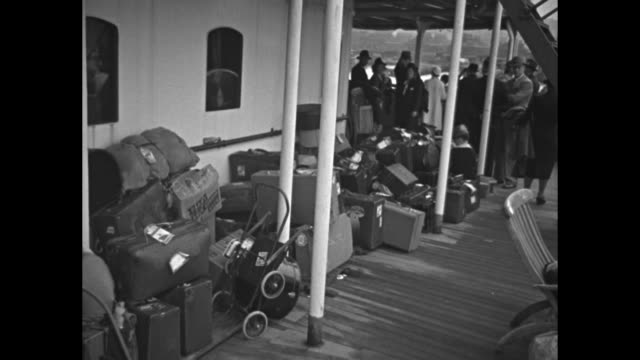 Washington in New York Harbor men in foreground watch / Americans returning from Britain stand on deck of ship / luggage and people on deck / 'Mrs...