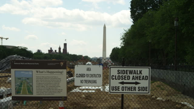 Washington Monument and Smithsonian Castle behind construction signs on National Mall in Washington DC. Shot in May 2012.