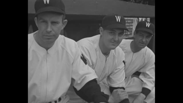 Washington Senators baseball players stand in dugout punching their mitts / camera pans players in dugout / panning CU of players Dutch Leonard Rick...