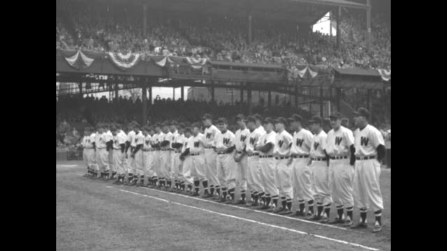 MS Washington Senators players holding movie cameras crowd in stands in bg / Washington players lined up on field stands in bg / Boston Red Sox...