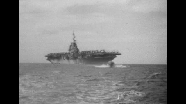 Wasp aircraft carrier at sea smaller ship moves diagonally from Wasp to camera Wasp is carrying USS Hobson survivors / QS jet takes off from Wasp /...