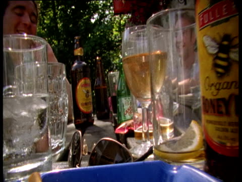 Wasp flies through empty glasses and bottles on picnic table in beer garden
