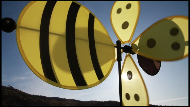 vidéos et rushes de wasp or bee windmill spinning in wind against blue sky, france, ardeche - jaune