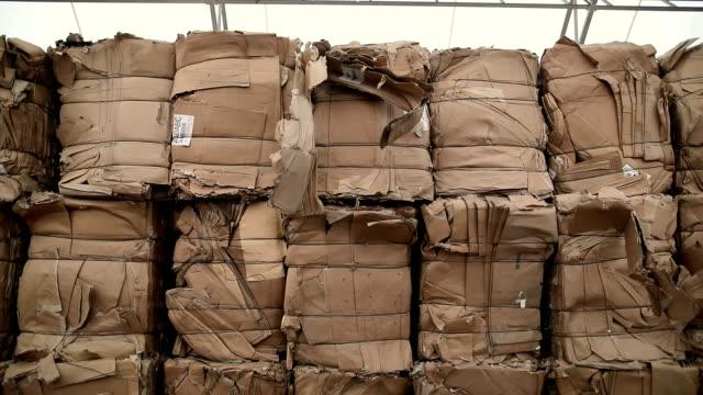 stockvideo's en b-roll-footage met afval karton wordt ingezameld en verpakt voor recycling. dump van oude gestapelde kartonnen doos. recycling center verzamelt cartoon dozen - karton