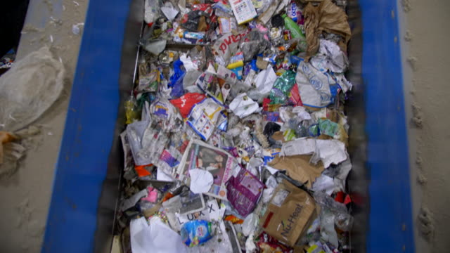waste conveyor belt in recycling plant full of plastics, paper and rubbish - plastförorening bildbanksvideor och videomaterial från bakom kulisserna
