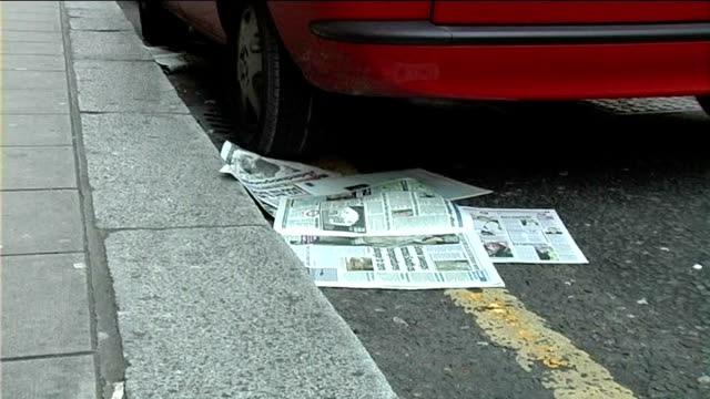 westminster council threatens to ban free newspapers; old newspapers scattered in gutter commuter along as taking newspaper from distributor - sidewalk gutter stock videos & royalty-free footage