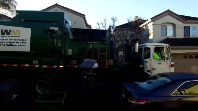 waste management garbage truck using mechanical arm to lift residential garbage bin at curbside in san ramon, california at dawn, 2019. - 廃棄物処理点の映像素材/bロール