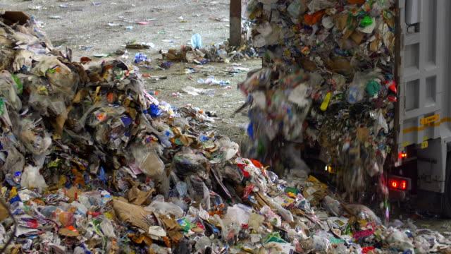 vídeos de stock, filmes e b-roll de waste truck dumps recycling plastics rubbish bottles and paper waste in recycling plant - depósito de lixo