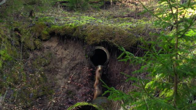 vidéos et rushes de traitement des eaux usées s'écoulant hors de la pipe - dépression terrestre