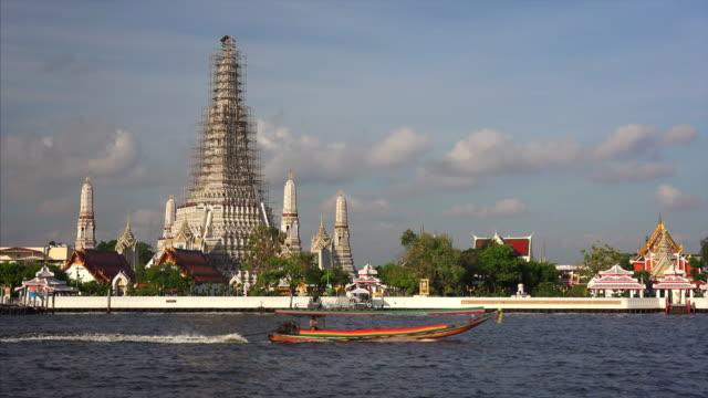 Wat Arun buddhist temple during renovation across the Chao Phraya River in Bangkok, Thailand