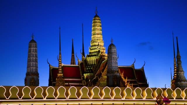 vidéos et rushes de wat phra kaew behind the grand palace wall lit during dusk - grand lit