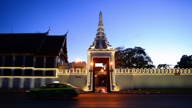 vidéos et rushes de wat phra kaew behind the grand palace wall lit during dusk with the sawatdi sopha - grand lit