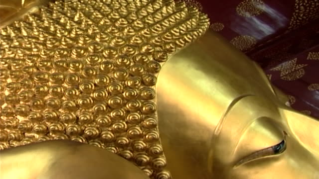 wat phra pathom chedi. close-up of the ringlets on the head of a golden reclining buddha statue in the western viharn of the temple. - curly stock videos & royalty-free footage
