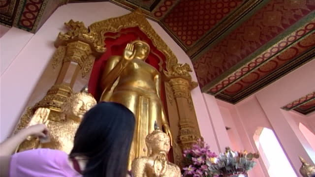 wat phra pathom chedi lowangle of a golden phra ruang buddha statue in the abhaya mudra pose believers make offerings seeking security and reassurance - lily stock videos & royalty-free footage