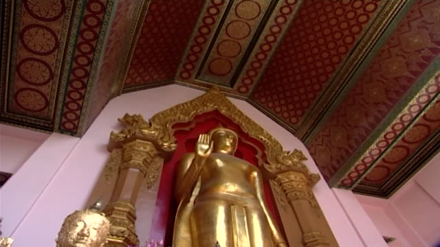 wat phra pathom chedi lowangle of a phra ruang standing buddha statue in abhaya mudra and an ornate ceiling decorated with lotus flower motifs - lily stock videos & royalty-free footage