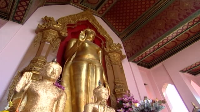 wat phra pathom chedi lowangle of a phra ruang standing buddha statue in abhaya mudra a posture that promotes fearlessness and protection - lily stock videos & royalty-free footage
