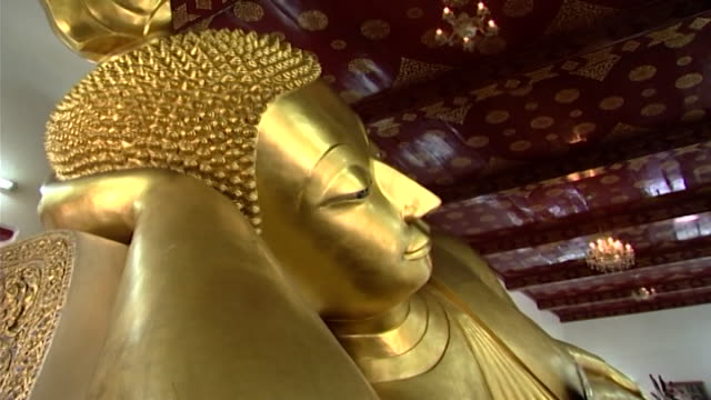 wat phra pathom chedi. low-angle view of the ringlets on the head of a golden reclining buddha in the western viharn of the temple. - curly stock videos & royalty-free footage