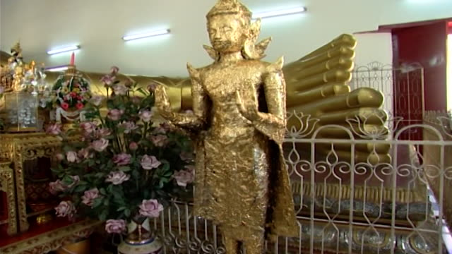 wat phra pathom chedi. mcu of a buddhist statue covered in gold leaf, which is placed on the statue by pilgrims, to honour buddha's teachings. - gold leaf stock videos & royalty-free footage