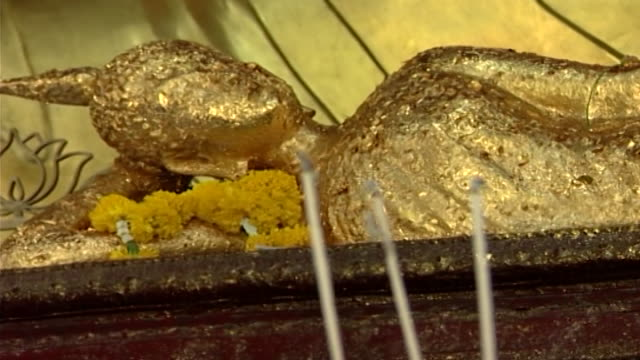 wat phra pathom chedi. rack-focus from a statue of a reclining buddha covered in gold leaf to burning incense sticks. - gold leaf stock videos & royalty-free footage