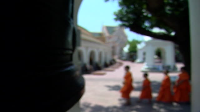 wat phra pathom chedi. rack-focus on a tolling bell as novice monks walk single file. buddhists ring bells, callling the faithful to prayer and... - harmony stock videos & royalty-free footage