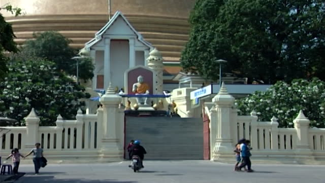 wat phra pathom chedi. view of a buddha statue seated at entrance to the great pagoda in the vitarka mudra pose. - pagoda stock videos & royalty-free footage