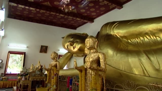 wat phra pathom chedi. view of a reclining buddha statue, in the western viharn, flanked by smaller statues covered in gold leaf. - gold leaf stock videos & royalty-free footage