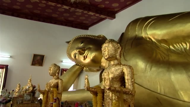 wat phra pathom chedi. zoom-in to the golden face of a reclining buddha behind a smaller standing buddha covered in gold leaf. - gold leaf stock videos & royalty-free footage