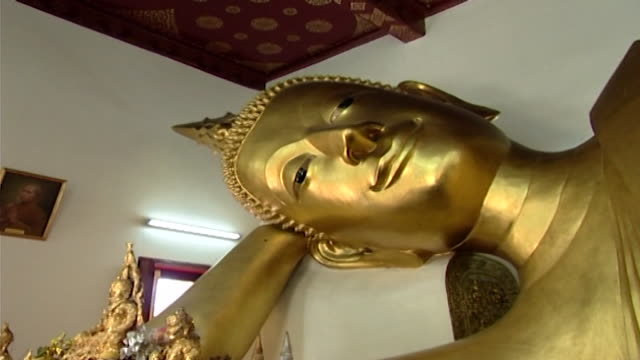 wat phra pathom chedi. zoom-in to the mother-of-pearl eye of a reclining golden buddha in parinirvana pose, in the western viharn of the temple. - buddha stock videos & royalty-free footage