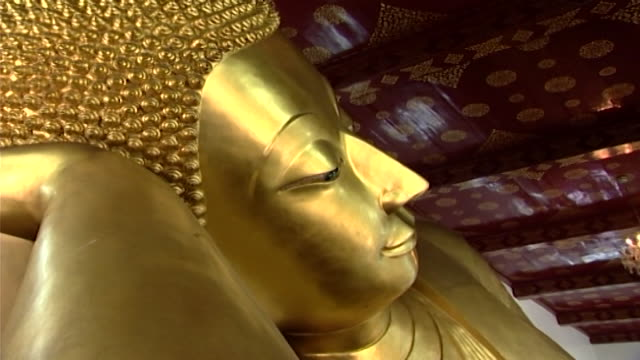 wat phra pathom chedi. zoom-in to the mother-of-pearl eye of a reclining golden buddha, in the western viharn of the temple. - curly stock videos & royalty-free footage