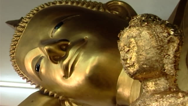 wat phra pathom chedi. zoom-out revealing a reclining buddha statue, in the western viharn, flanked by smaller statues covered in gold leaf. - gold leaf stock videos & royalty-free footage