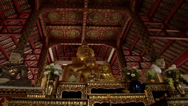 wat phra singh. view of a golden buddha statue on a butsudan, surrounded by other buddha and deva statues, beneath a mandala-adorned gabled ceiling. - mandala stock videos & royalty-free footage