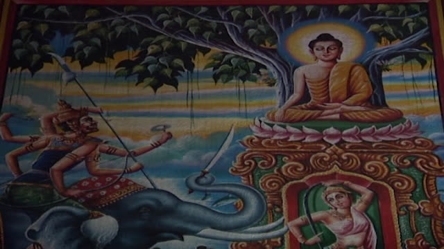 wat suan dok temple. low-angle of a painting depicting buddha resisting the temptations of mara, a demon attempting to seduce him. - cross legged stock videos & royalty-free footage