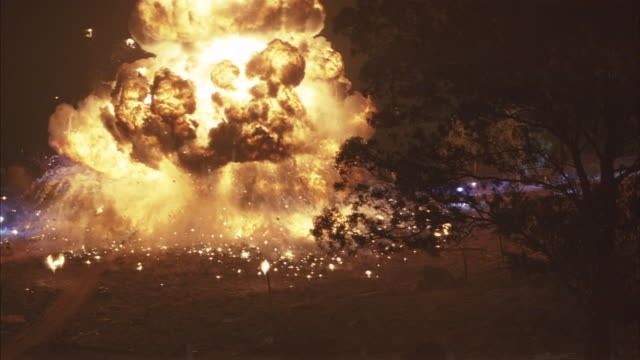A watch tower explodes and burns at night.
