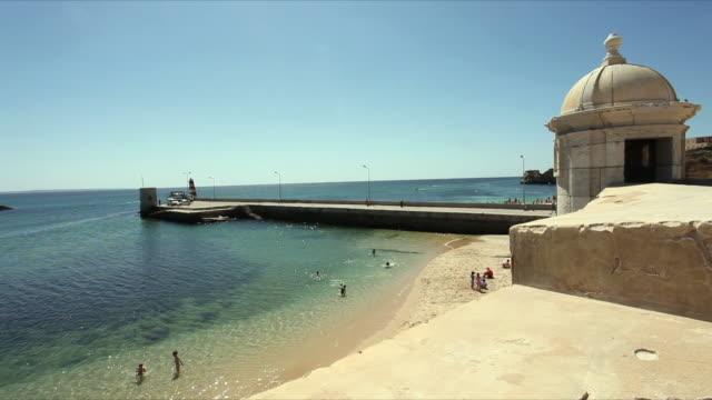 ws watch tower of forte da ponta da bandeira and beach with pier / lagos, portugal - algarve stock-videos und b-roll-filmmaterial