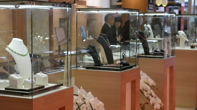 Watches are displayed for sale at the Laox Co Ginza store in Tokyo Japan on Thursday Nov 28 An employee assists a customer at the watch counter Pan...