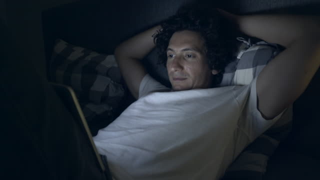vídeos de stock e filmes b-roll de watching a movie in the middle of night. - homens de idade mediana