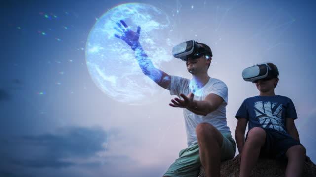 vidéos et rushes de regarder l'hologramme de la terre à l'aide de casque vr assis à l'extérieur - cinémagraphie