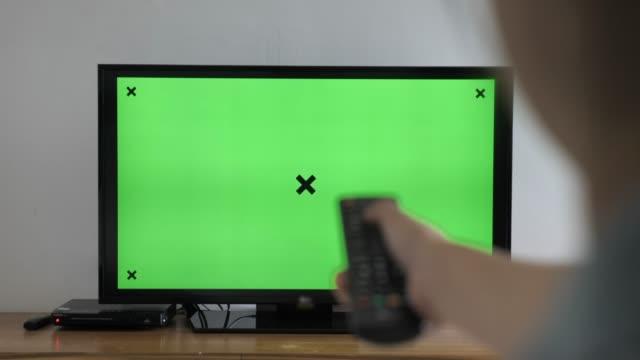 グリーンスクリーンテレビを見て、自宅でチャンネルを変更 - テレビ放送点の映像素材/bロール