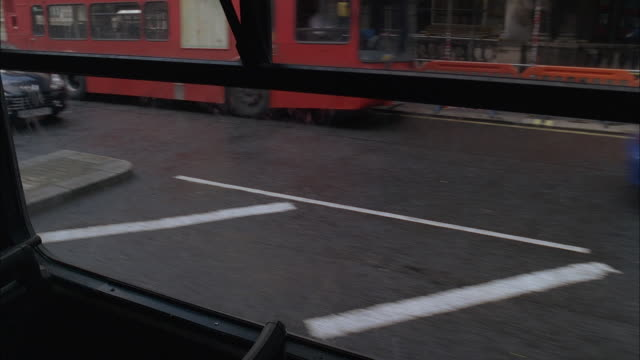 POV Watching through bus window as bus leaves stop, and car turning at intersection, slamming into bus, breaking the window, and accelerating away / London, England, United Kingdom