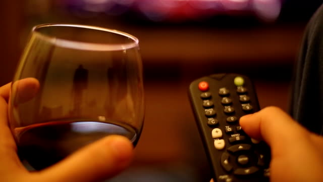 vídeos de stock e filmes b-roll de ver televisão com um copo de vinho - canal mar